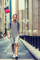 Young Russian Man traveling in New York, wearing black, white striped long sleeve T shirt, shorts, sneakers, shoulder carrying bag, cap backward, walking on vintage narrow street. Retro filtered look.