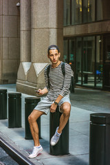 Russian Man traveling in New York, wearing black, white striped long sleeve T shirt, shorts, sneakers, shoulder carrying bag, cap backward, sitting on metal pillar on street, texting, looking around..