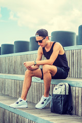 Man travels in New York in hot summer, wearing black tank top, shorts, white sneakers, cap worn backward, sits on wooden stairs at park, bag beside him, reads messages on cell phone. Filtered effect..