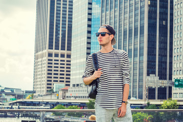 Young Man travels in New York, wearing striped long sleeve T shirt, sunglasses, cap worn backward, shoulder carrying bag, stands in business district with high buildings. Filtered look with soft light