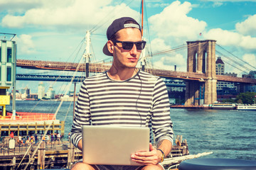 Russian man travels, works in New York, wearing striped long sleeve T shirt, cap worn backward, sunglasses, sits by East River, works on laptop computer, listens music with earphone. Filtered effect..