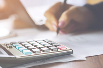 blur background business woman hand woman hand calculating her monthly expenses with calculator in foreground