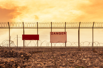 metal mesh wall with barbed wires  and rolled razor barbed wires security fence and danger notice board on sunset background
