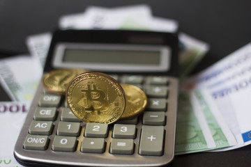 Golden bitcoins and banknotes Euro on a calculator on a black background. the new virtual money
