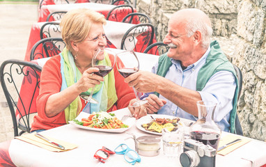 Retirement senior couple drinking and eating in restaurant outdoor - Mature Husband and wife having fun in romantic vacation- Love and joyful elderly lifestyle concept - Warm contrast filter