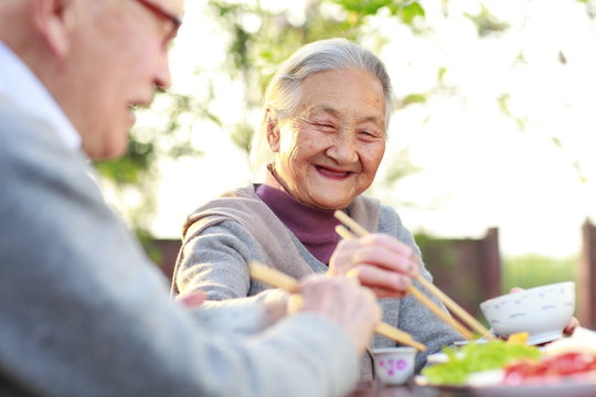 Happy senior asian couple having meal in the yard
