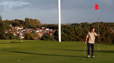 A golfer removes the flag stick at Sandhills golf club in Glasgow East, in Glasgow
