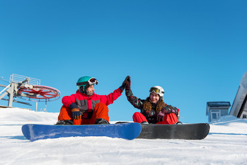 Couple of snowboarders gives a high five to each other while sitting on the snow tops of a slope against a blue sky and ski lift on the background at winter ski resort on a sunny day