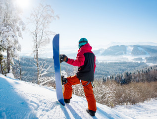 Rear view of snowboarder standing on top of a slope looking around enjoying the view at winter ski resort Bukovel in the sunny morning the the mountains copyspace landscape lifestyle concept
