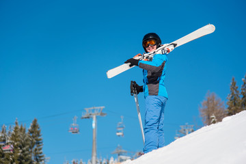 Low angle shot of a woman standing on the hill in snowy mountains, carrying her skis on her shoulder, smiling to the camera copyspace lifestyle sportswoman recreation weekend resort winter concept