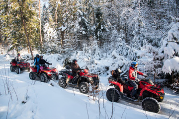 Group of people driving off-road four-wheelers ATV bikes in beautiful winter forest