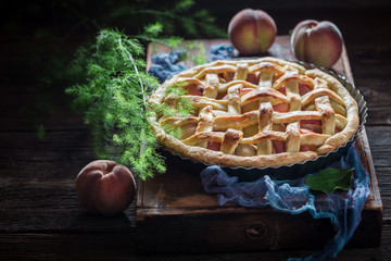 Tasty and hot tart with peaches on blue cloth