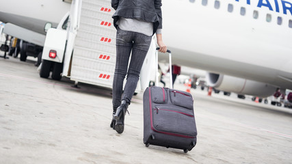Passenger walking  in the airplane with suitcase
