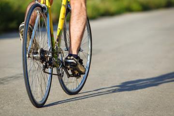 Detail of cyclist man feet riding bike on road.