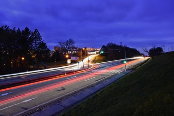 Night photo traffic on the road. Evening landscape with cars. Cars with lights and blurred color lines.