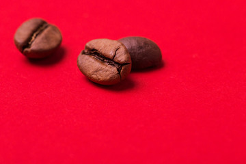 Roasted coffee beans on red background. Color surge trend.