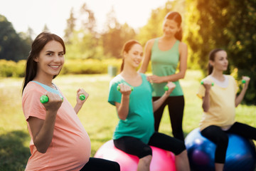 Pregnancy yoga. Three pregnant women are engaged in fitness in the park. They sit on balls for yoga