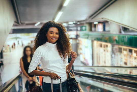 Portrait of young beautiful woman on stairs in airport.