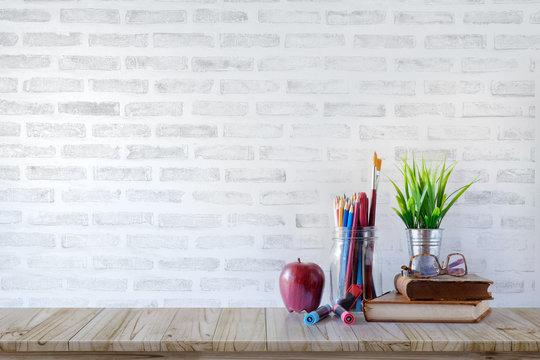 School supplies on white brick background.