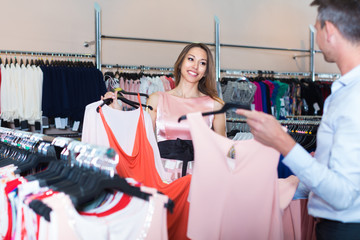 Young woman and man are choosing dress for her