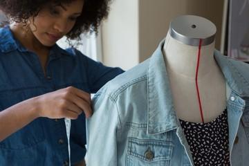 Female designer measuring the length of denim on mannequin
