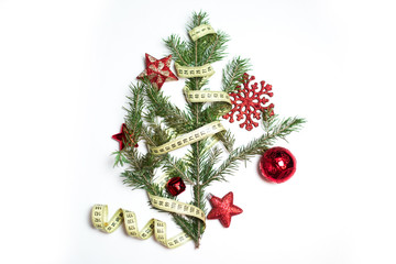 Fir branch (christmas tree) with tailor's meter and red new year balls isolated on white background