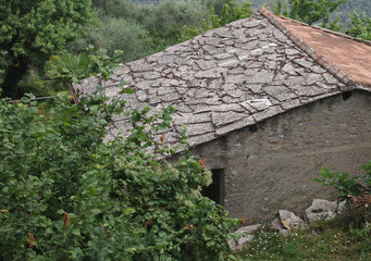 old house with flat stone roof tiles in Mediterranean area