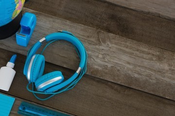 Headphone with other stationery on wooden table