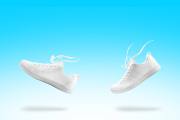 Pair of White sneaker composition like walking and floating rope isolated on blue and white gradian background with clipping path