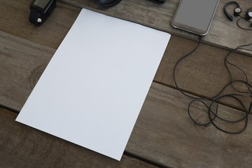 Paper with electronic device kept on wooden table