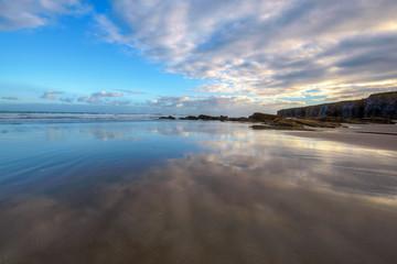 Cielo azul  reflejado en el agua de la playa