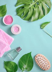 Spa background, flat lay layout with monstera leaves and cosmetic care products
