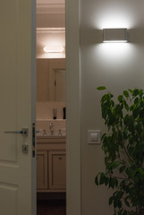 Wall LED lamps in the interior. Open white door to the bath