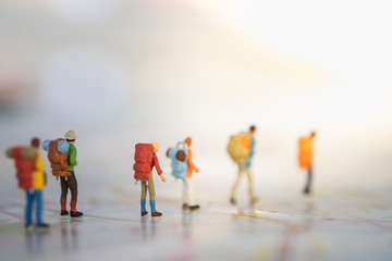 Travel Concept. Group of  traveller miniature figures with backpack walking on street map.