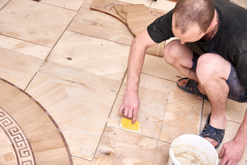 The carpenter applies glue with a notched trowel on the plywood.