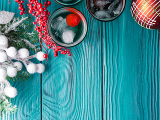 Christmas holiday party green alcohol drinks with cherry. Festive aperitif shots and ornaments on wooden dark table