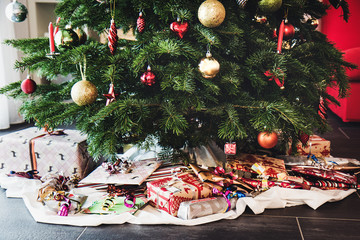 Lower part of Christmas tree with different presents lying underneath