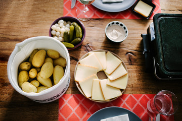 Swiss traditional dish called raclette including steamy potatoes, melted cheese and pickles eaten at christmas and wintertime
