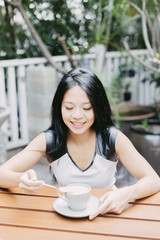 Young Indonesian woman having coffee outdoor