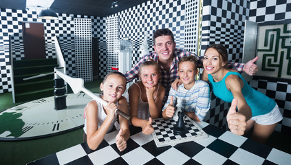 Family with children are visiting stylized chess room
