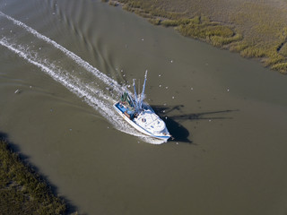Aerial view of commerical fishing vessel coming into port.
