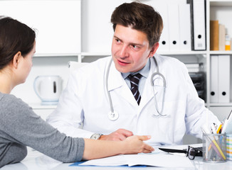 Cheerful professional doctor in uniform talking with patient