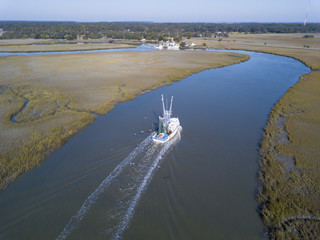 Aerial view of shrimp boat coming into port.