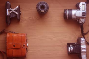 cámaras antiguas, objetivo y funda sobre madera. Fondo para web fotográfica