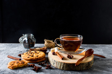 Cup of  tea, biscuits, cinnamon, anise on dark   background