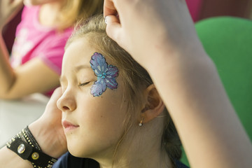 little girl draw a butterfly on her face