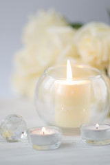 Big palm candle in glass ball with white roses