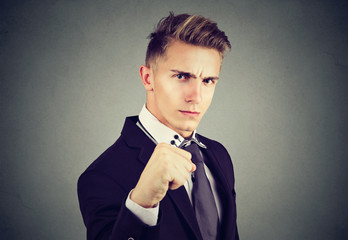 Angry business man with closed fist looking at camera on gray background