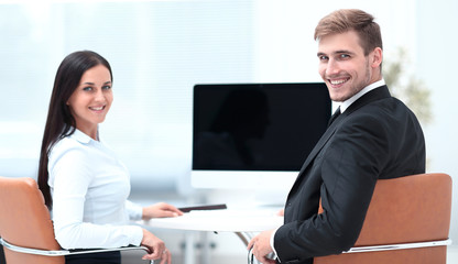 two successful employee sitting behind a Desk