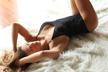 Sexy woman in black body lying on white fur.